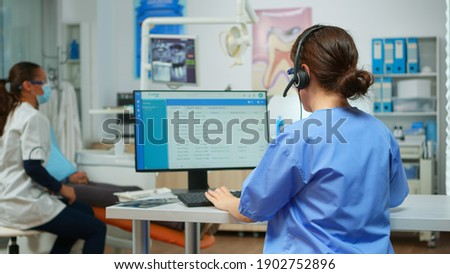 Dentist assistant making appointments using headset sitting in front on computer while doctor is working with patient in background examining teeth problem. Nurse taking notes in stomatological office Stock photo ©