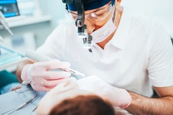 Dentist cleans tooth canals of patient and removes nerve - pulpitis treatment