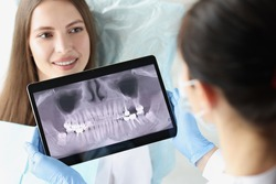Dentist doctor examines x-ray of female patient jaw