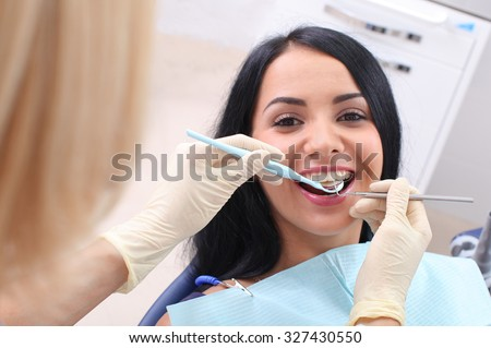 Dentist examining a patient's teeth in the dentist. #327430550