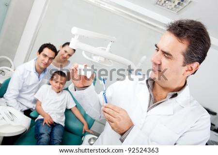 Dentist explaining how to brush teeth on a prosthesis