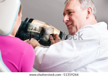 Dentist explaining the details of a x-ray picture to his patient, focus on eyes of doctor