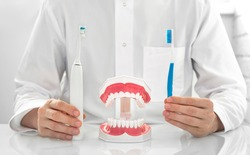 Dentist holding two toothbrushes for cleaning teeth, manual and electric ultrasound. What kind of toothbrush to use