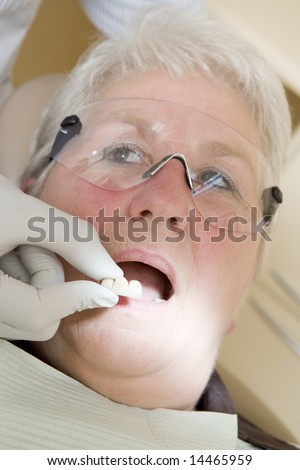 Dentist in exam room fitting dentures on woman in chair