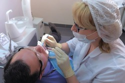 Dentist is applying blue gel on man's teeth to find dental tartar and caries. Hygiene care for oral cavity, prophylactic cleaning of teeth in dentistry, stomatology clinic. Saliva ejector in mouth.