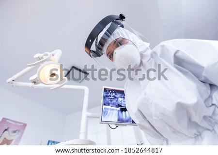 Dentist point of view wearing protection gear against covid outbreak during treatment in dental office. Stomatolog wearing safety gear against coronavirus during heatlhcare check of patient. Photo stock ©
