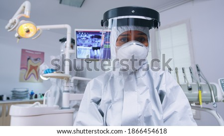 Dentist pov in covid suit examining mouth hygine using dental tools in stomatological office with new normal. Stomatolog wearing safety gear against coronavirus during heatlhcare check of patient. Photo stock ©