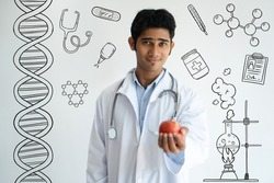 Dentist showing apple to camera with hand drawn medical sketches. Smiling successful young nutritionist with stethoscope on neck giving recommendation about food. Doctor concept