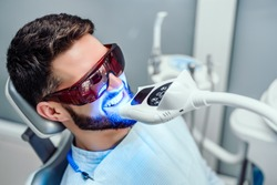Dentist starting teeth whitening procedure with young man.
