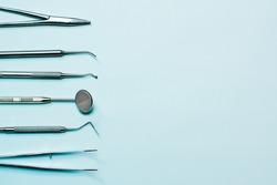 Dentist tools on light blue background: corncang, curette, dental probe, gross-mayer clamp, dental mirror and explorer. Dental hygiene and healthcare concept.