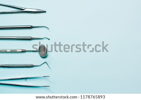 Dentist tools on light blue background: corncang, curette, dental probe, gross-mayer clamp, dental mirror and explorer. Dental hygiene and healthcare concept.