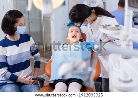 Dentist using modern dental equipment for little girl treatment in clincic. Dentistry specialist during child cavity consultation in stomatology office using modern technology. Stock foto ©