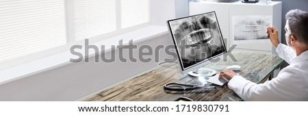 Dentist Using Oral Software Looking At Teeth Xray On Desktop Computer Foto stock ©