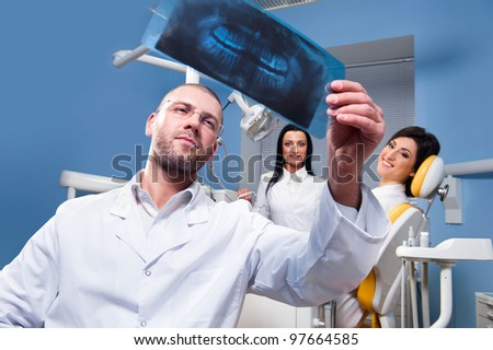 Dentist with x-ray and smiling patient with assistant in the background