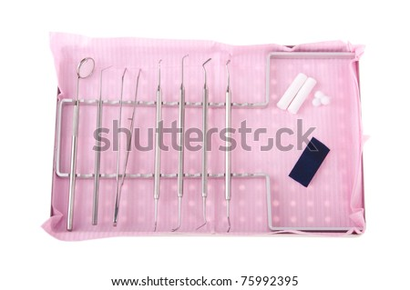 dentistry kit in a tray on pink bib (surgery instruments, articulation paper, cotton rolls and wools)