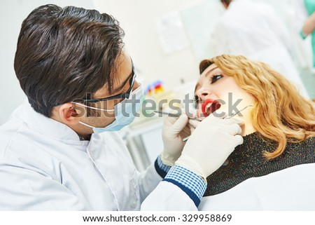 Dentistry. male asian dentist examining patient teeth in clinic
