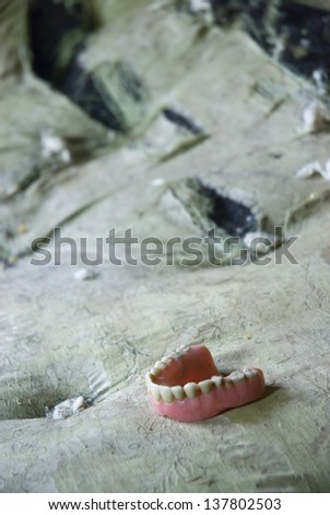 dentures on a mattress inside the home of a hoarder.