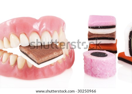Dentures with candy isolated on a white background.