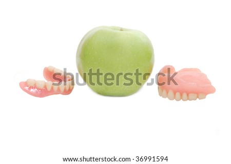 Dentures with green apple, isolated on a white background