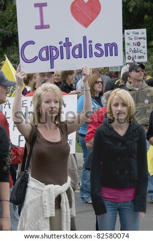 """DENVER, COLORADO – APRIL 15: Two women holding their """"I Love Capitalism"""" sign at a Tea Party Patriots Tax Day Rally in Downtown Denver, April 15, 2011"""