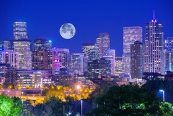 Denver Colorado at Night. Denver Downtown Skyline and the Full Moon on Clear Sky.