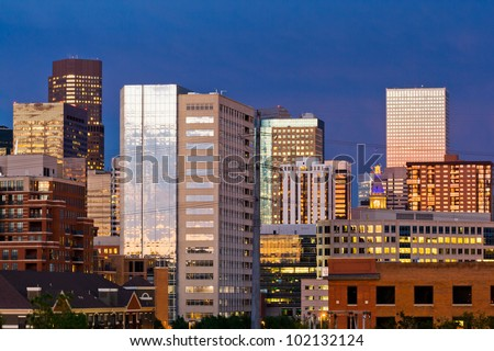 Denver skyline at dusk with colorful sunset reflection in the windows