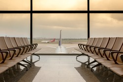 Departure lounge at the airport with seats in a row, plane and red dramatic sky behind the windows.