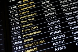 Departures display board at airport terminal showing international destinations flights to some of the world's most popular cities. Business or leisure travel concept