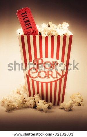 Depiction Of The Fifties Cinema Era With A Vintage Red Striped Old Popcorn Box Overflowing With Buttered Popcorn Coupled With A Movie Ticket - stock photo