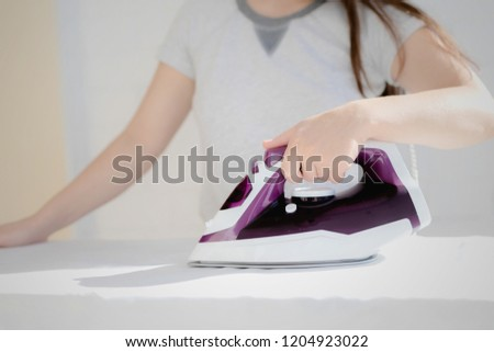 depicts the process of ironing clothes, visible iron, clothes, ironing board #1204923022