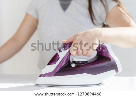 depicts the process of ironing clothes, visible iron, clothes, ironing board #1270894468