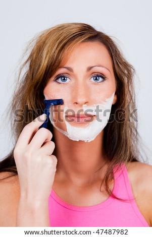 Depilating female looking in mirror