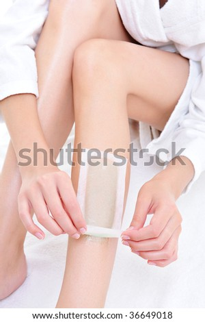 depilation on the part of female legs with waxing - white background