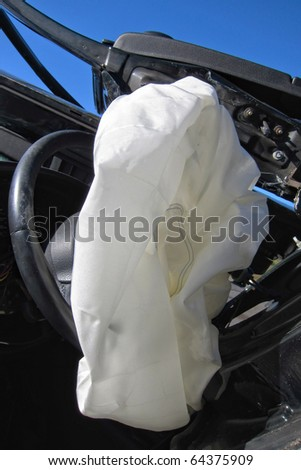 Deployed and deflated crash safety air bag in a heavily damaged wrecked car after a violent traffic accident