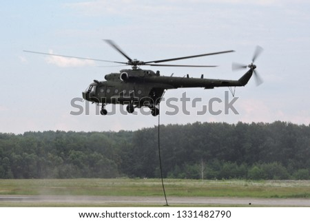 Deploying troops from a military helicopter using fast-roping technique