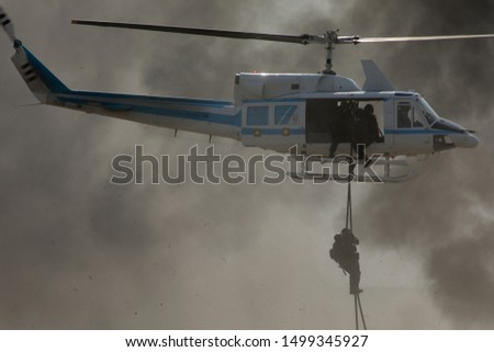 Deploying troops from a military helicopter using fast-roping technique. Special forces landing