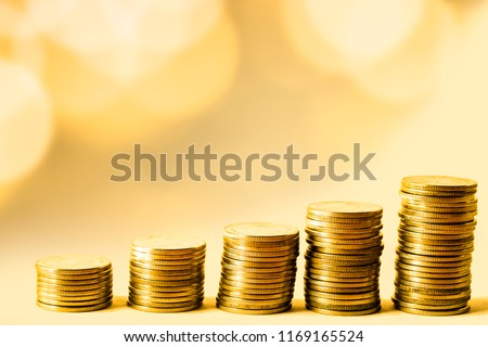 Deposit coins as an investment concept. It is growing to make rich and wealth. It is on table in front of golden bokeh background. Accumulate or income concept. it is passive income from interest.