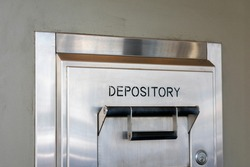 Depository sign on an exterior secured bank drop box attached to the wall of a bank building