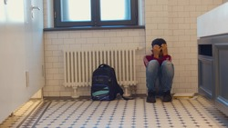 Depressed african child abandoned in lavatory and leaning against wall. Young afro boy sitting alone with sad feeling at school. Bullying, discrimination and racism concept