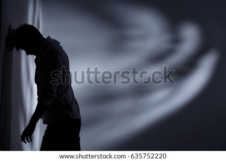 Depressed and broken man standing alone close to the wall #635752220