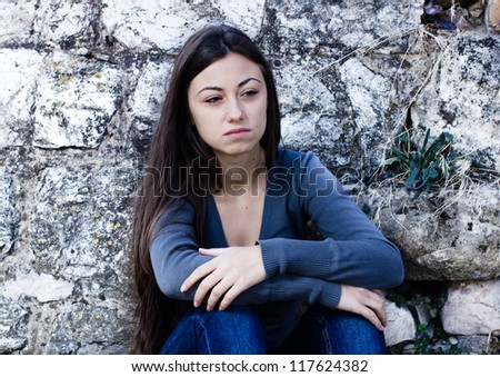 Depressed and lonely teenage girl, sad expression face, leaning on stone wall.