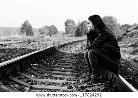 Depressed and lonely teenage girl with hands over her face sitting on the railroad
