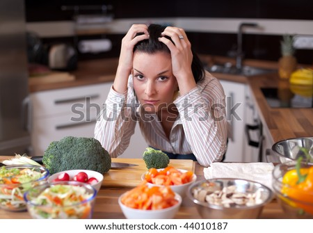 Depressed and sad young woman in kitchen