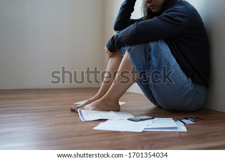 Depressed and stressed young asian woman meet financial problem and no money to pay credit card debt bill after unemployed from company financial crisis effect and COVID-19 virus epidemic feel worried Stock photo ©
