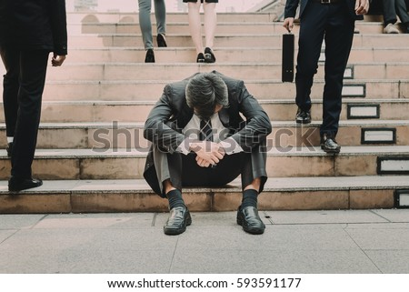 Depressed and tired businessman sitting at stair in city