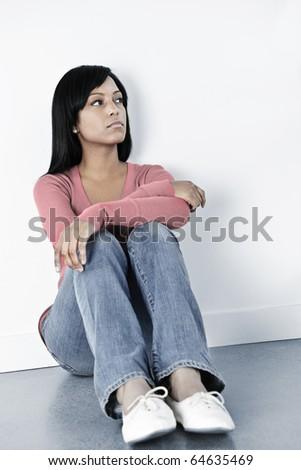 Depressed black woman sitting against wall on floor looking away
