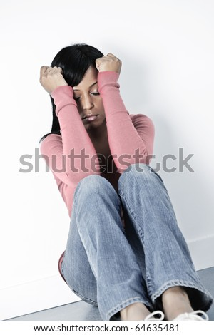 Depressed black woman sitting against wall on floor with eyes closed