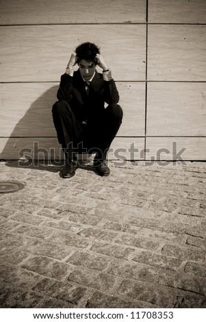 Depressed businessman in urban background, sepia toned.