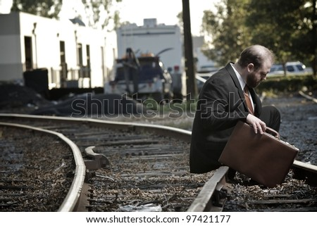 Depressed businessman sitting on railroad tracks