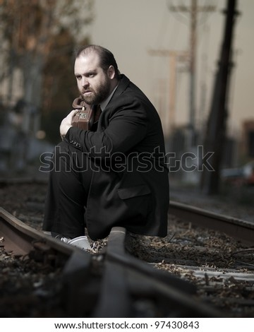 Depressed businessman sitting on railroad tracks - stock photo